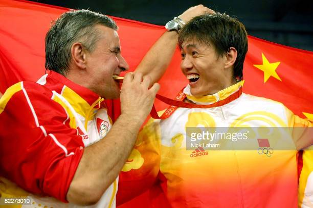Zhong Man of China smiles as his coach Christian Bauer bites his gold medal for the men's fencing individual sabre held at the Fencing Hall of...