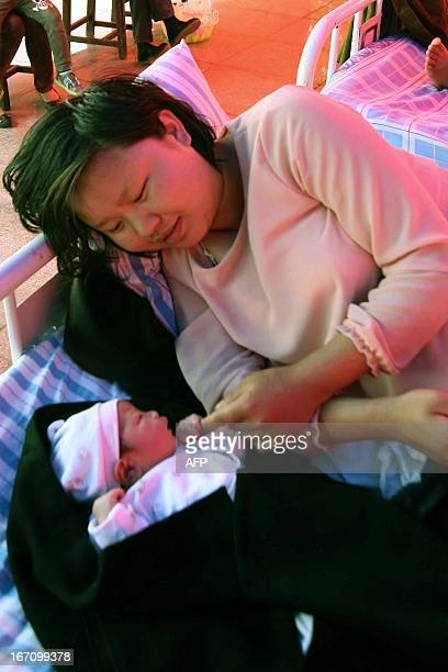 Zhou Chunzhi lies on a bed in a tent with her newborn baby in a village in Qionglai township after a shallow earthquake at magnitude 70 hit the city...