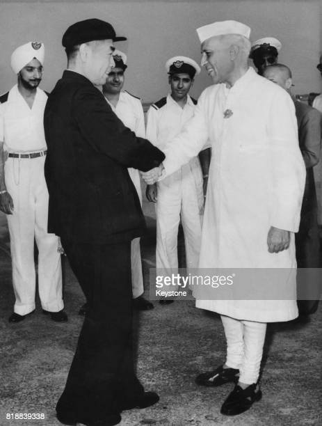Zhou Enlai Premier of the People's Republic of China is greeted by Indian Prime Minister Jawaharlal Nehru at the Indian Air Force Station in Palam...