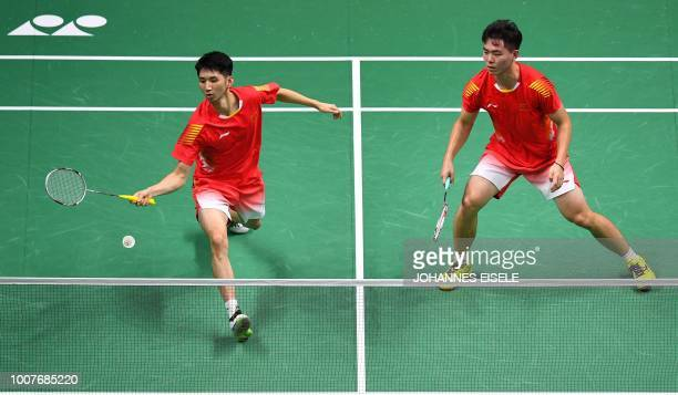 Zhou Haodong of China hits a shot beside teammate Han Chengkai against Milosz Bochat and Adam Cwalina of Poland in their men's doubles match during...