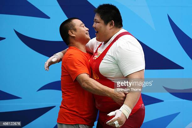 Zhou Lulu of China celebrates with her coach Yang Shi Jun after winning the Gold medal and breaking the world record for the Clean & Jerk following...