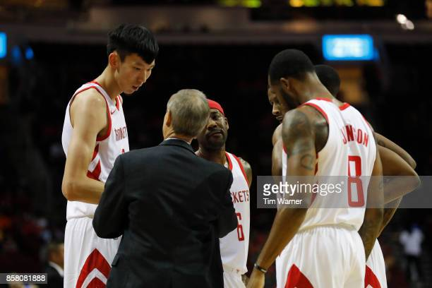 Zhou Qi of Houston Rockets talks with with assistant coach Jeff Bzdelik in a huddle in the second half against the Shanghai Sharks at Toyota Center...