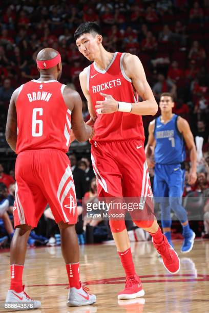 Zhou Qi of the Houston Rockets and Bobby Brown of the Houston Rockets react after a play during the game against the Dallas Mavericks on October 21...