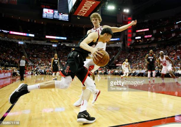 Zhou Qi of the Houston Rockets drives to the basket defended by Lauri Markkanen of the Chicago Bulls in the second half at Toyota Center on March 27...