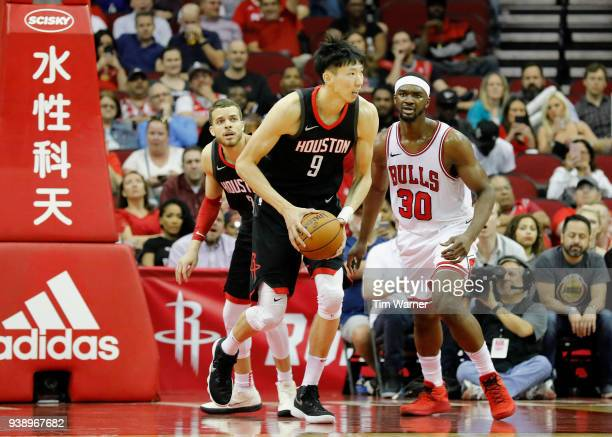 Zhou Qi of the Houston Rockets grabs a rebound in the second half defended by Noah Vonleh of the Chicago Bulls at Toyota Center on March 27 2018 in...