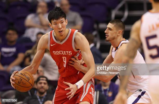 Zhou Qi of the Houston Rockets handles the ball against Alex Len of the Phoenix Suns during the second half of the NBA game at Talking Stick Resort...
