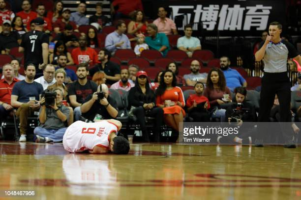 Zhou Qi of the Houston Rockets holds his knee after an injury in the first half of the preseason game against the the Shanghai Sharks at Toyota...