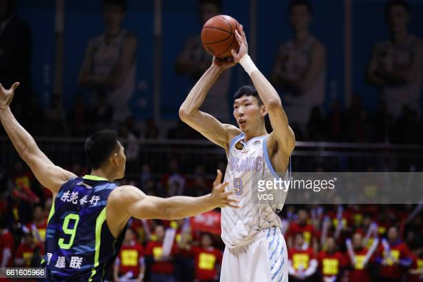 Zhou Qi of Xinjiang Flying Tigers handles the ball against Yi Jianlian of Guangdong Southern Tigers in Game One of the 2017 CBA Finals at Hongshan...