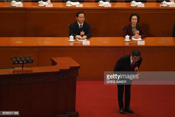 Zhou Qiang president of the Supreme People's Court bows to delegates before delivering the work report during the second plenary session of the first...