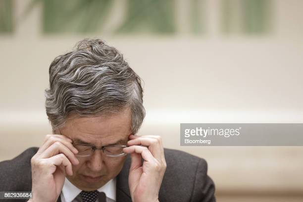 Zhou Xiaochuan, governor of the People's Bank of China , adjusts his glasses during a news conference at the Great Hall of the People during the 19th...
