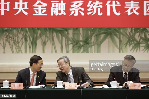 Zhou Xiaochuan governor of the People's Bank of China center speaks with Liu Shiyu chairman of the China Securities Regulatory Commission left as Guo...