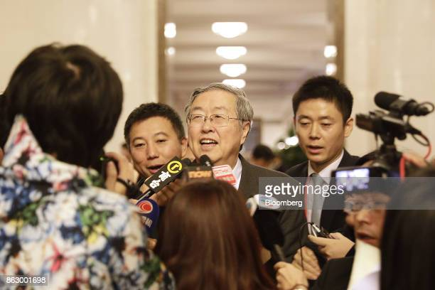 Zhou Xiaochuan, governor of the People's Bank of China , center, speaks to members of the media following a news conference at the Great Hall of the...