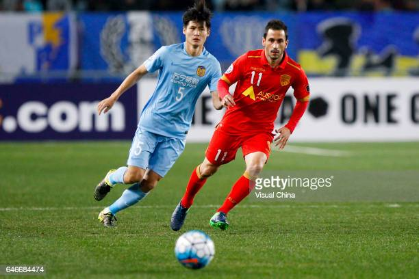 Zhou Yun of Jiangsu Suning and Marcelo Carrusca of Adelaide United follow the ball during the AFC Champions League 2017 Group H match between Jiangsu...