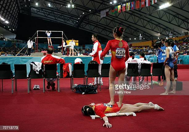 Zhou Zhuoru of China stands to massage her teammate He Ning of China during the Women's Individual AllAround Final at the 15th Asian Games Doha 2006...