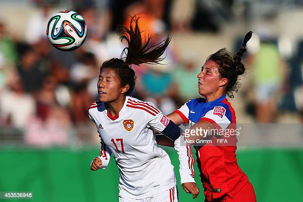 Zhu Beiyan of China PR is challenged by Cari Roccaro of the United States during the FIFA U20 Women's World Cup Canada 2014 group B match between the...