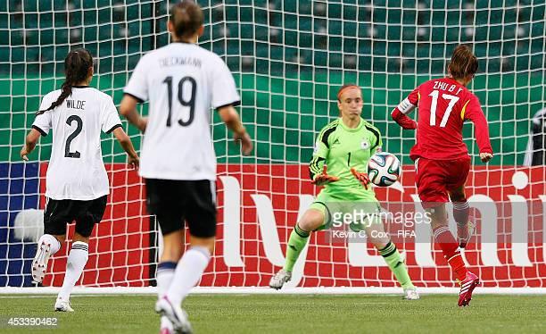 Zhu Beiyan of China PR scores a goal past goalkeeper Meike Kaemper of Germany during the FIFA U20 Women's World Cup Canada 2014 Group B match between...