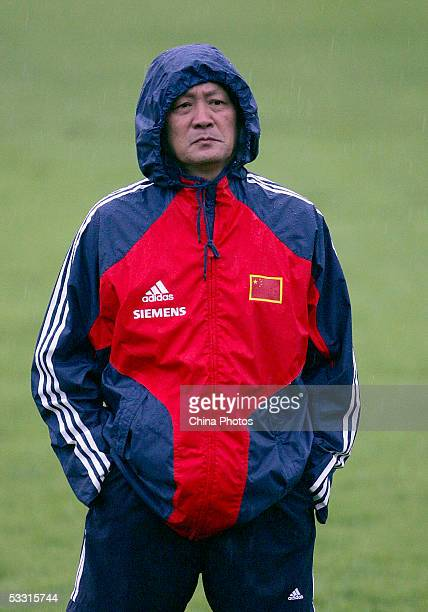 Zhu Guanghu, coach of Chinese National Football Team, watches the Chinese players training during a practice session for the East Asian Football...