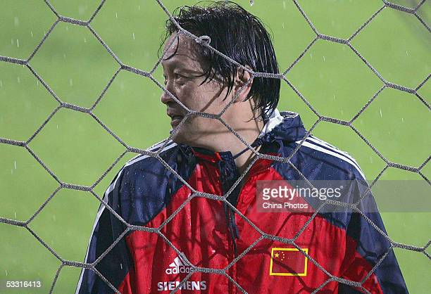 Zhu Guanghu, coach of Chinese National Football Team, watches the Chinese players training in rain during a practice session for the East Asian...