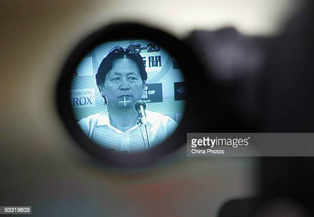 Zhu Guanghu, head coach of Chinese National Football team, is seen through the viewer of a camera at a press conference after a match between China...