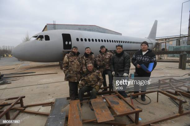 Zhu Yue and his team pose for a photo in front of the homemade Airbus A320 jet plane at an open space in Tieling, Liaoning Province of China....