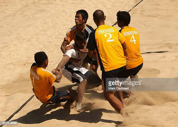 Ziaur Rahman of Bangladesh is tackled by the Indonesian team in their Beach Kabaddi match on day four of the 2008 Asian Beach Games at Benoa Beach on...
