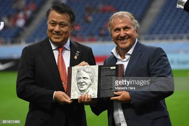 Zico is presented the plaque by the Japan Football Association President Kozo Tashima during the Japan Football Hall of Fame Award Ceremony prior to...