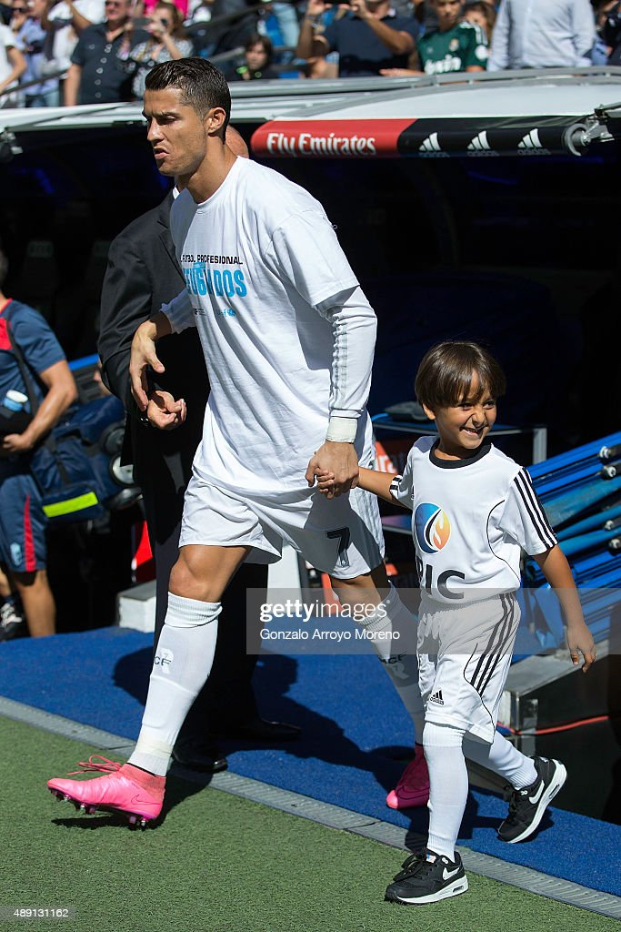 Zied (R), the son of the Syrian refugee Osama Alabed Almohse, both attacked by the Hungarian camera operator Petra Laszlo, acces the pitch in company of Cristiano Ronaldo (L) of Real Madrid CF prior to start the La Liga match between Real Madrid CF and Granada CF at Estadio Santiago Bernabeu on September 19, 2015 in Madrid, Spain.