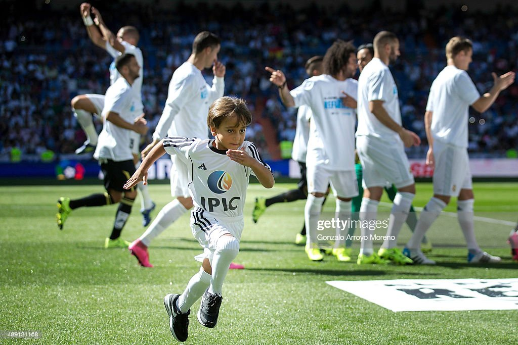 Zied, the son of the Syrian refugee Osama Alabed Almohse, both attacked by the Hungarian camera operator Petra Laszlo, runs out the pitch after posing with Real Madrid CF players prior to start the La Liga match between Real Madrid CF and Granada CF at Estadio Santiago Bernabeu on September 19, 2015 in Madrid, Spain.