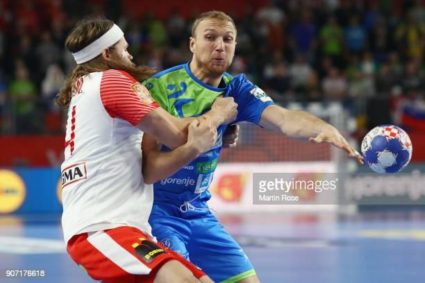 Ziga Mlakar of Slovenia is challenged by Mikkel Hansen of Denmark during the Men's Handball European Championship main round group 2 match between...