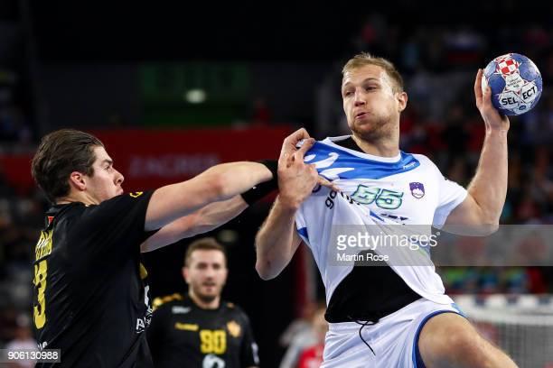 Ziga Mlakar of Slovenia is challenged by Vladan Lipovina of Montenegro during the Men's Handball European Championship Group C match between...