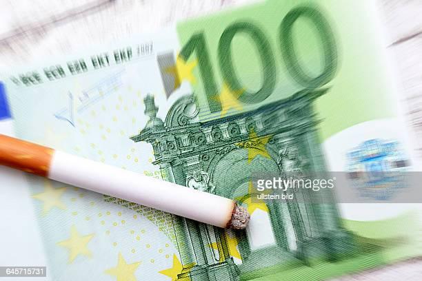 Zigarette auf EinhundertEuroGeldschein Symbolfoto Erhöhung der Tabaksteuer