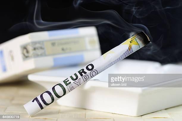 Zigarette aus 100EuroSchein Symbolfoto Tabaksteuer