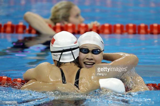 Zige Liu of China congratulates gold medalist Liuyang Jiao of China after she won the Women's 200m Butterfly Final during Day Thirteen of the 14th...