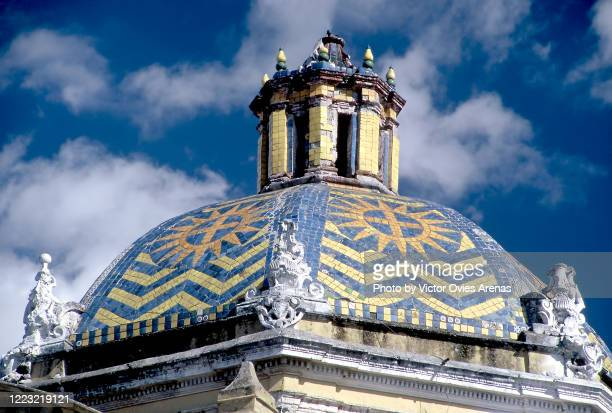 zigzag patterning of blue and yellow tiles atop the octagonal dome of the church of the parish of san josé in puebla, mexico - victor ovies fotografías e imágenes de stock
