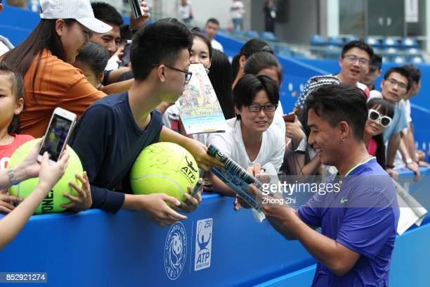 Zihao Xia of China signs autograph for supporters after the match against Mate Pavic of Croatia during Qualifying second round of 2017 ATP Chengdu...