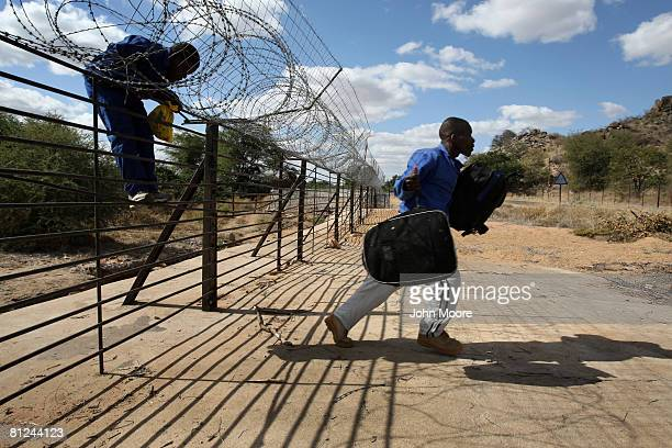 Zimbabwaen immigrants climb through a barbed wire fence while illegally crossing illegally into South Africa May 27 2008 near Musina South Africa...