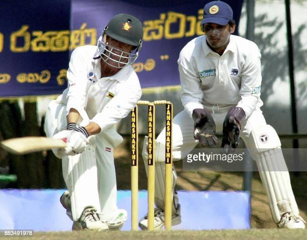 Zimbabwe batsman Gavin Rennie sweeps a ball as Sri Lankan wicketkeeper Kumar Sangakkara looks on during the fourth day of the second cricket Test...