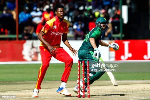 Zimbabwe bowler Blessing Muzarabani watches as Pakistan batsman Asif Ali goes for quick runs during the first T20 cricket match between Pakistan and...