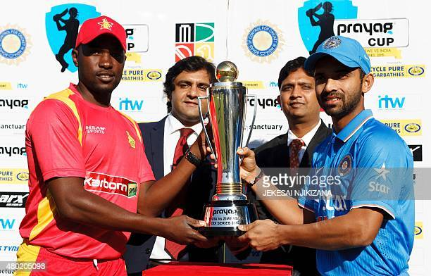 Zimbabwe captain Elton Chigumbura holds the series trophy with India captain Ajinkya Rahane ahead of the first One Day International cricket match...