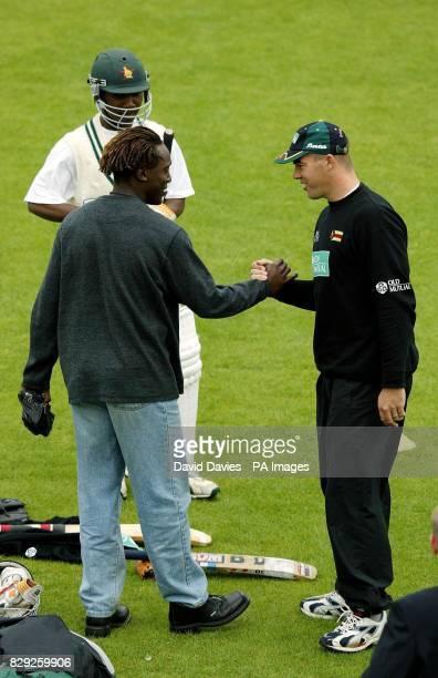 Zimbabwe captain Heath Streak meets former Zimbabwe test star Henry Olonga during practice at Lords.