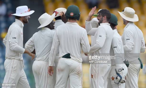 Zimbabwe cricket captain Graeme Cremer celebrates with teammates after dismissing Sri Lankan cricket captain Dinesh Chandimal during the fourth day...