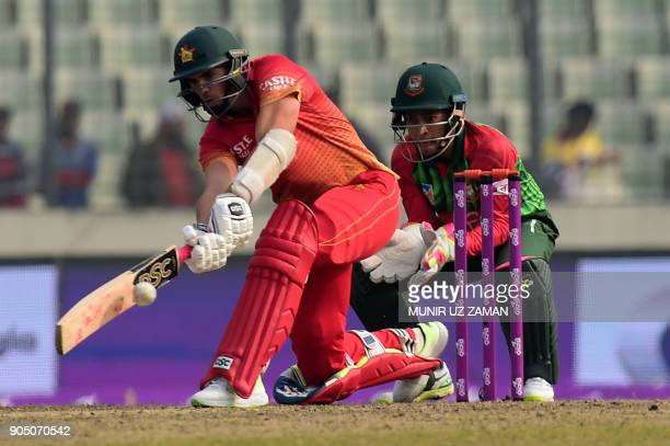 Zimbabwe cricket captain Graeme Cremer plays a shot as Bangladeshi wicketkeeper Mushfiqur Rahim looks on during the first One Day International...