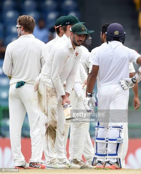 Zimbabwe cricket captain Graeme Cremer Sri Lankan cricketer Niroshan Dickwella speak during the final day of a oneoff Test match between Sri Lanka...