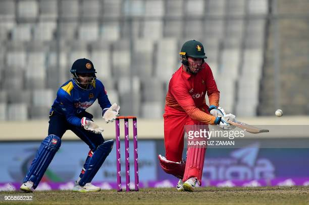 Zimbabwe cricketer Brendan Taylor plays a shot as Sri Lankan wicketkeeper Dinesh Chandimal looks on during the second One Day International cricket...