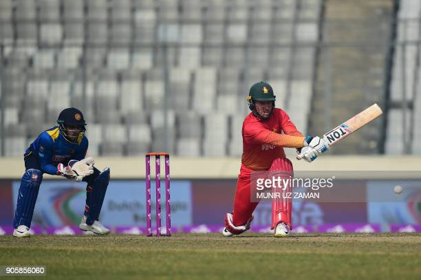 Zimbabwe cricketer Brendan Taylor plays a shot as Sri Lankna wicketkeeper Dinesh Chandimal looks on during the second One Day International cricket...