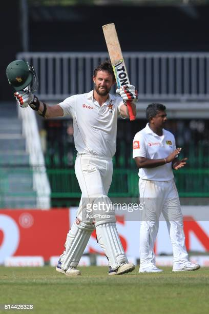 Zimbabwe cricketer Craig Ervine celebrates his century as Sri Lanka's Rangana Herath acknowledges during the first day of the only Test cricket match...
