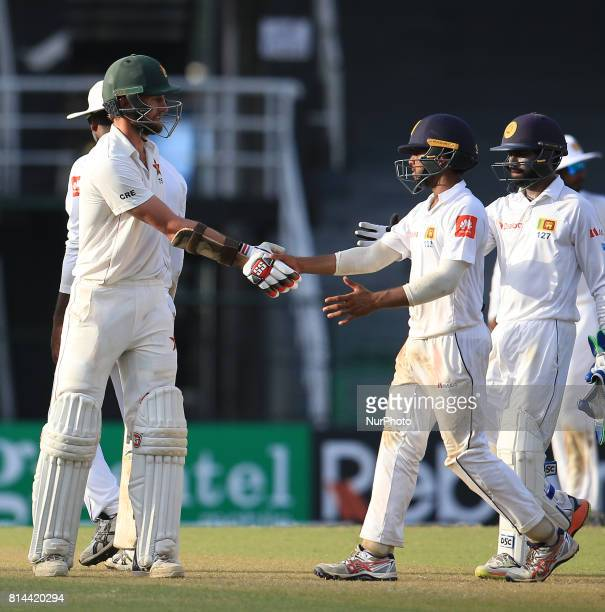Zimbabwe cricketer Craig Ervine is congratulated by Sri Lankan cricketer Niroshan Dickwella after the 1st day's play of the only Test cricket match...