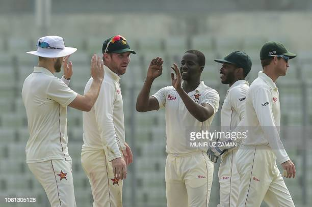 Zimbabwe cricketer Donald Tiripano celebrates with his teammate after the dismissal of the Bangladesh cricketer Mushfiqur Rahim during the fourth day...