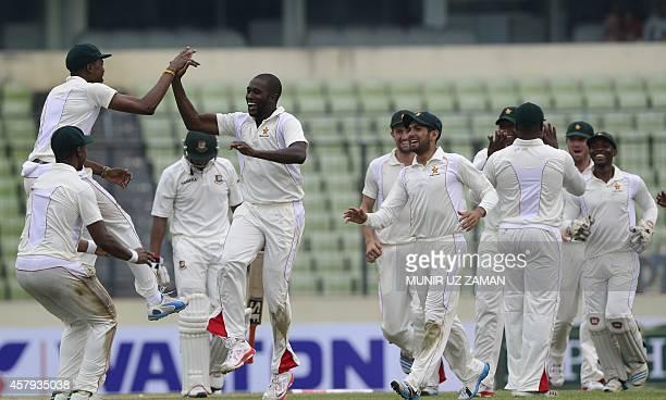 Zimbabwe cricketer Elton Chigumbura celebrates with his teammates after the dismissal of Bangladeshi cricketer Mohammad Mahmudullah during the third...
