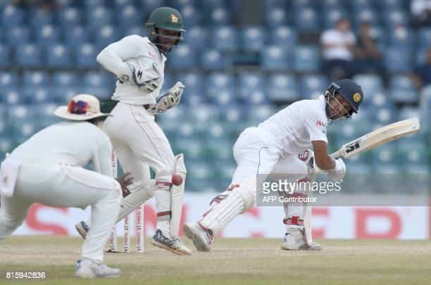 Zimbabwe cricketer Hamilton Masakadza catches the ball to dismiss Sri Lankan cricket captain Dinesh Chandimal as wicketkeeper Regis Chakabva looks on...